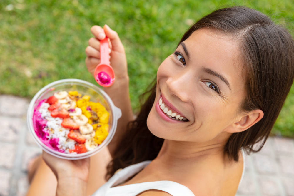 Acai bowl healthy eating Asian woman showing fruits smoothie breakfast outside in park for lunch. Diet vegan food closeup. Dragonfruit puree, bananas, strawberries, mangos, coconut, flax seeds.