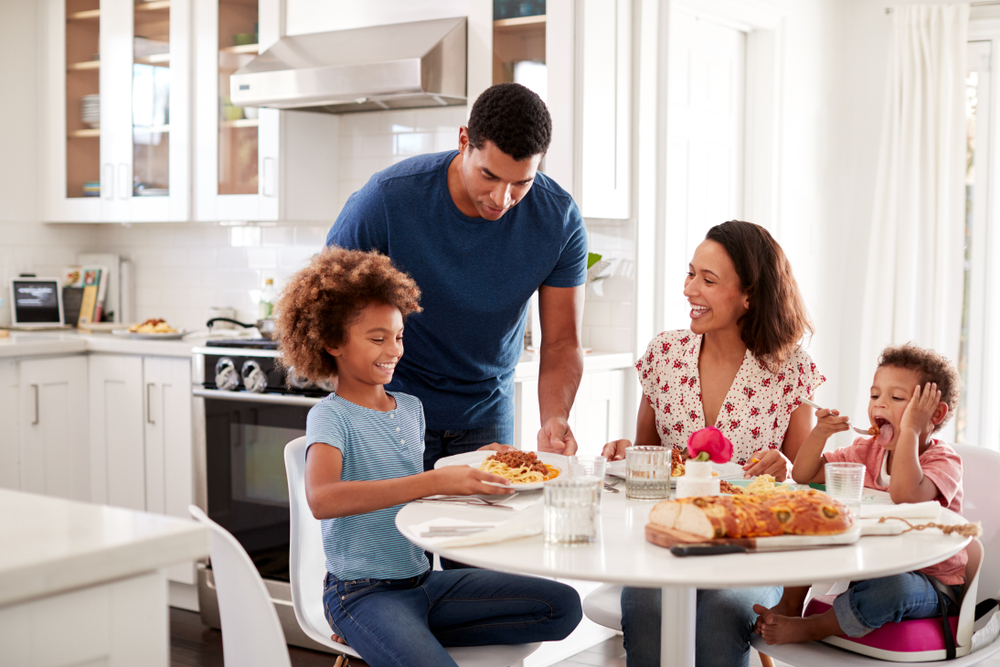 African American young mother sitting at table in the kitchen with children, father serving them food, selective focus