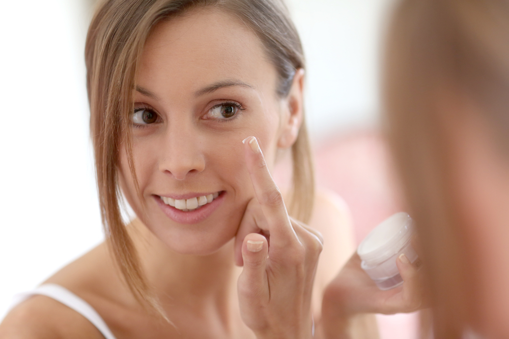 Woman putting anti-aging cream on her face