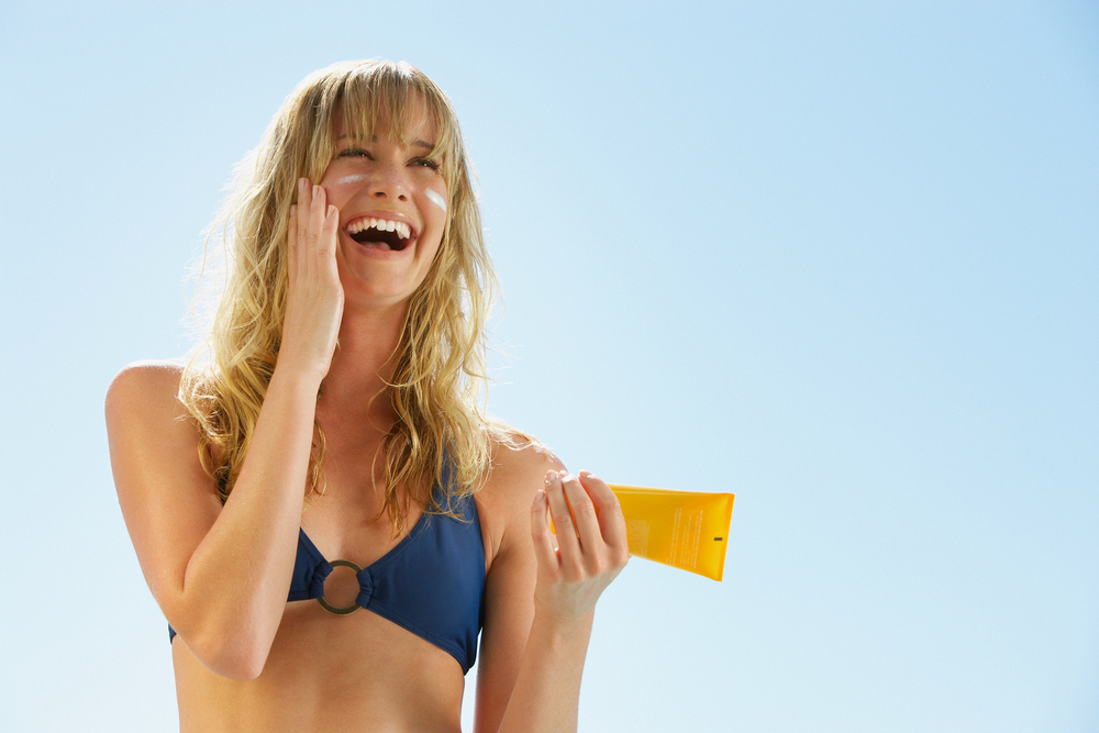 Woman with healthy skin applying sunscreen