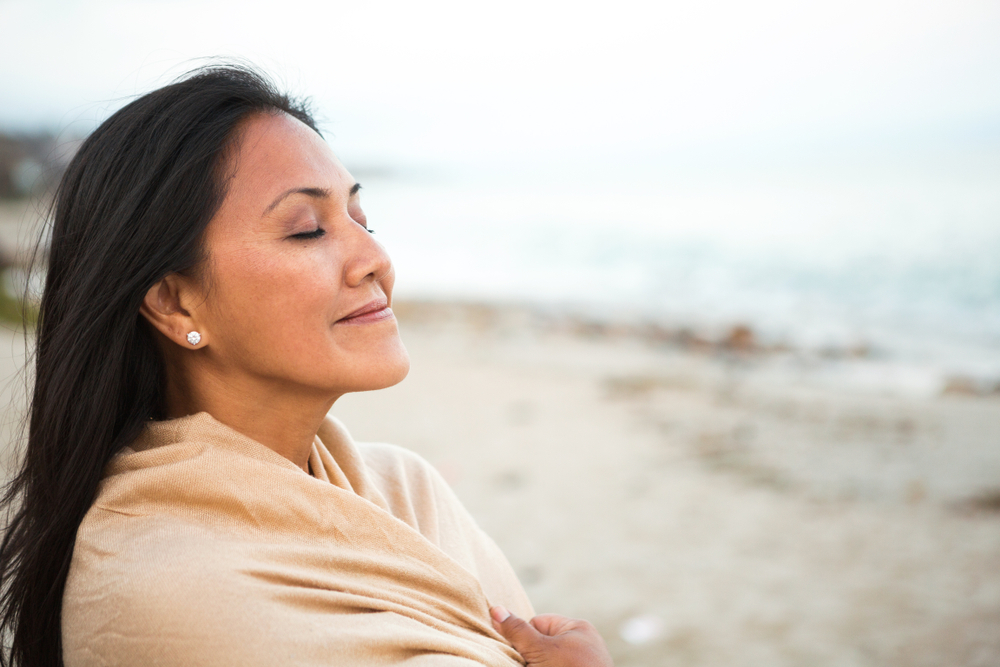 Woman helping to reduce the risk of premature sun damage wearing a shawl smiles on the beach.