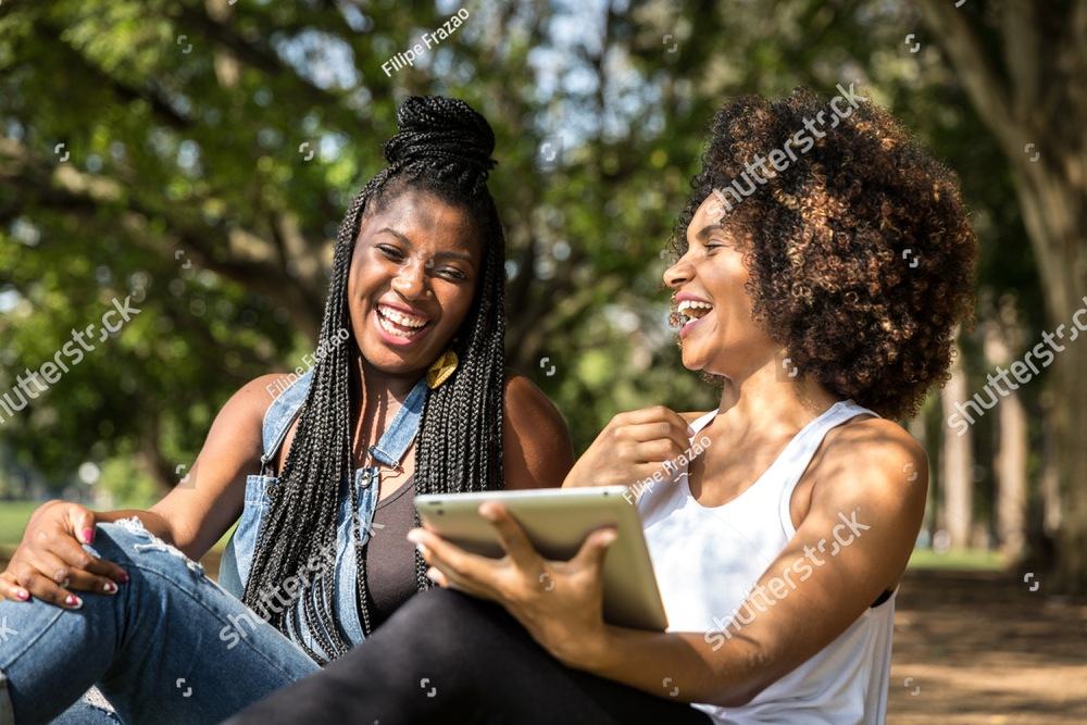 Brazilian afro women using tablet computer in the park