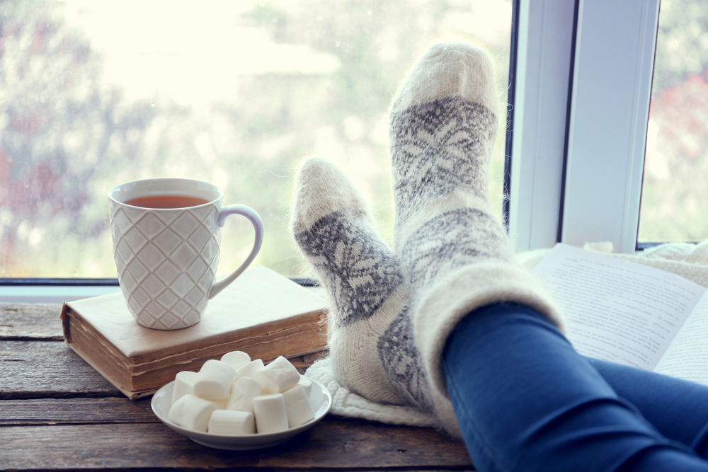 Closeup of a woman resting her feet on a windowsill next to a mug of hot tea and a book.