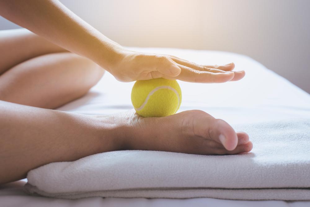 Woman massaging foot with a tennis ball.