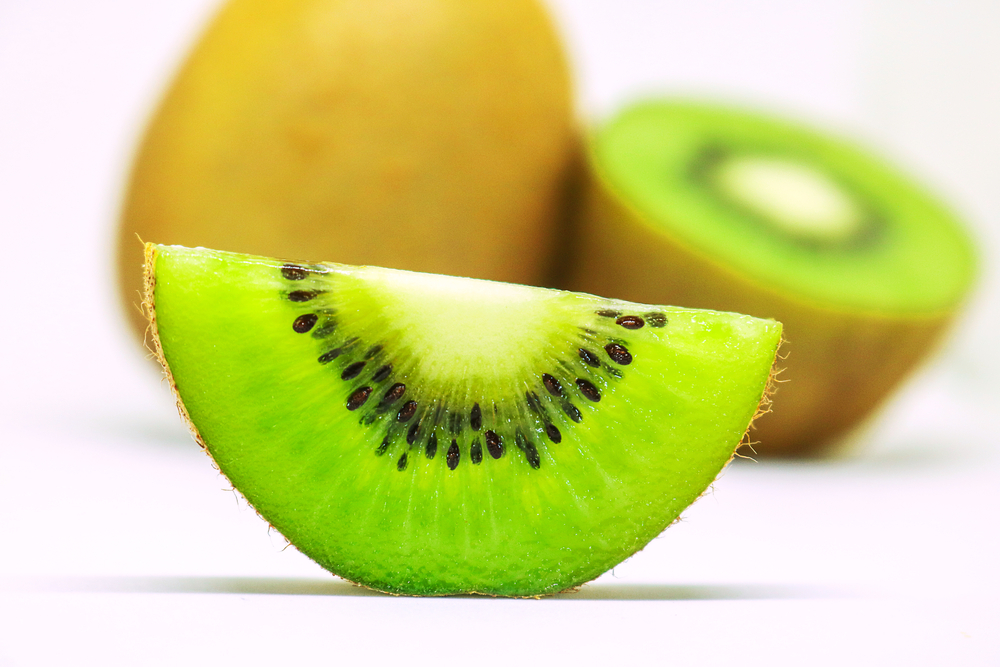 kiwi fruit sliced open on a white surface.