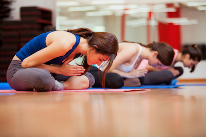 Group of cute Hispanic women relaxing and meditating during their yoga class in a gym