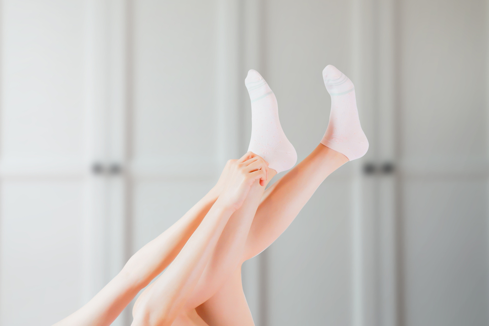 Woman applying moisturizer to her dry, cracked feet.