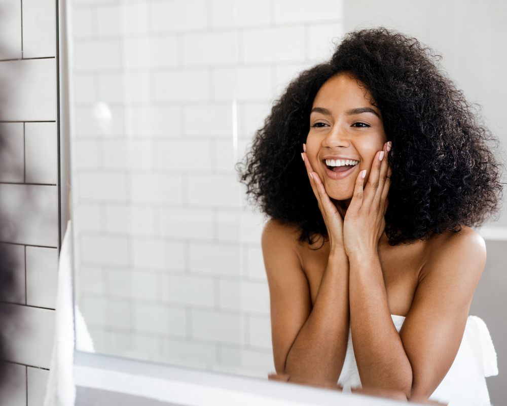 Happy woman admiring her skin in front of the bathroom mirror, touching face with hands