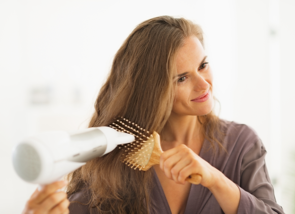Woman drying hair in the bathroom