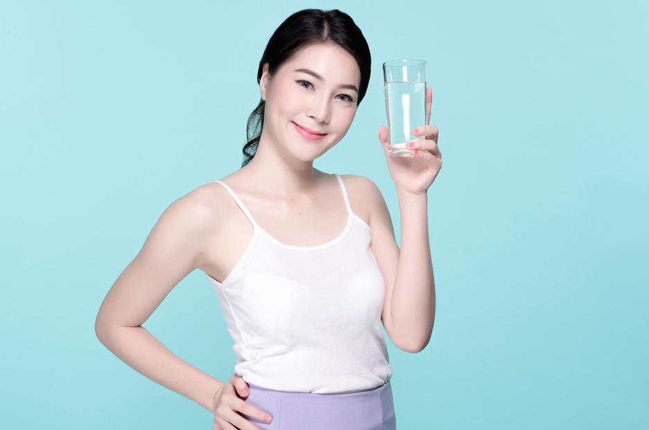 Healthy asian young beautiful woman drinking water, beauty face natural makeup, isolated over blue background.