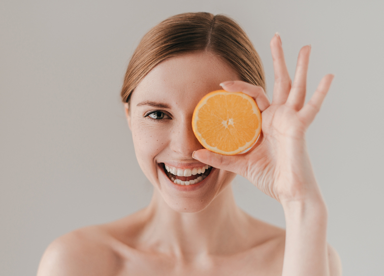 woman holding vitamin C-rich orange slice.