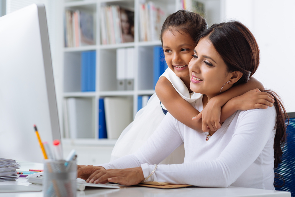working mom at a desk while her daughter hugs her