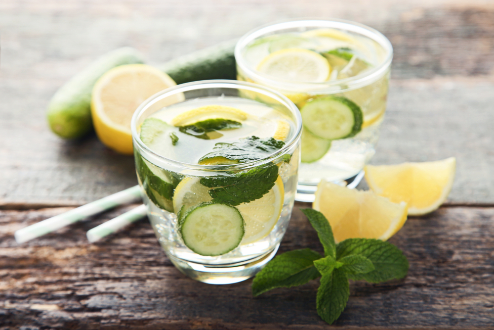 Lemonade with cucumbers, lemons and mint leafs in glasses on wooden table