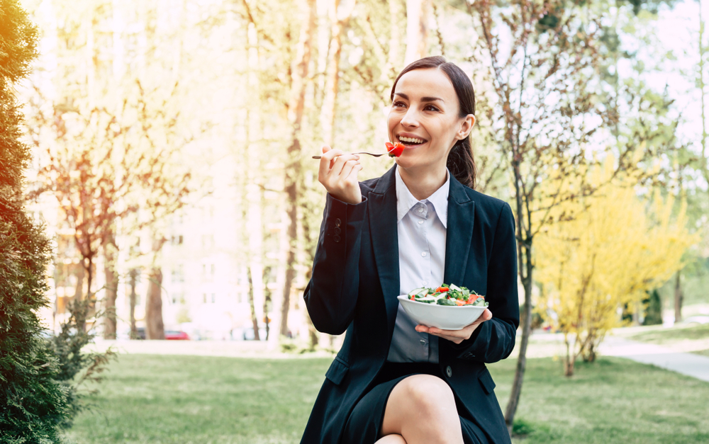 Lunch in the fresh air. Modern beautiful business woman in a black suit eating a salad with fresh vegetables sitting on a bench near an office building