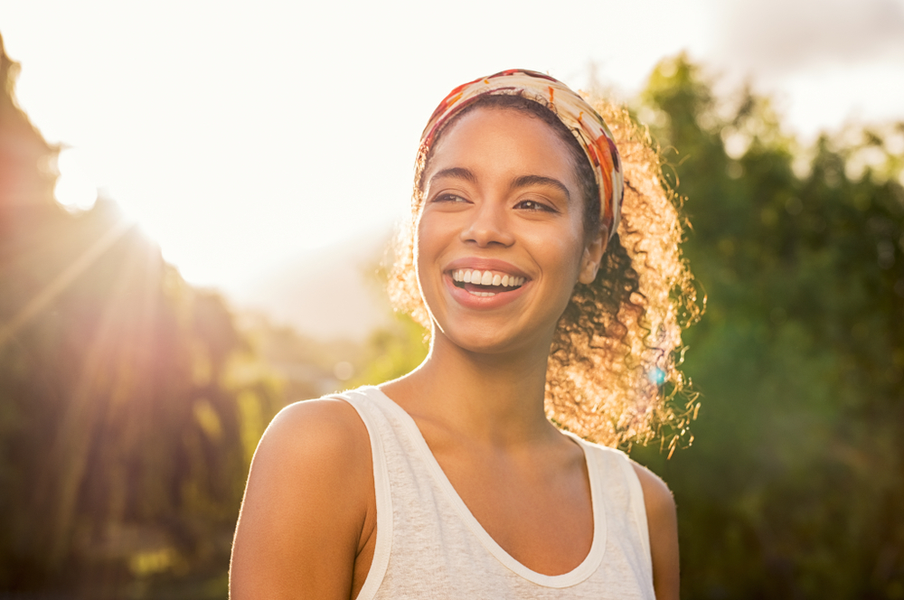 A smiling woman stands in the sunlight reaping the benefits of the sun.