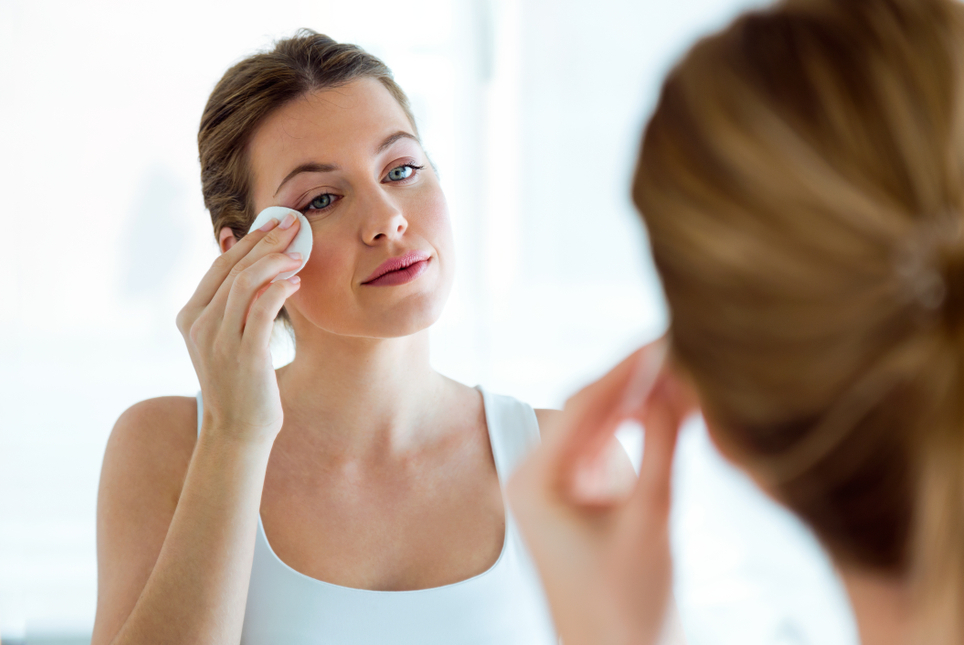 Portrait of beautiful woman is cleaning her face while looking in the mirror in the bathroom.