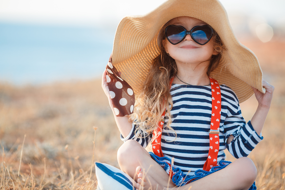 A young girl sits near the beach wearing a sun hat.