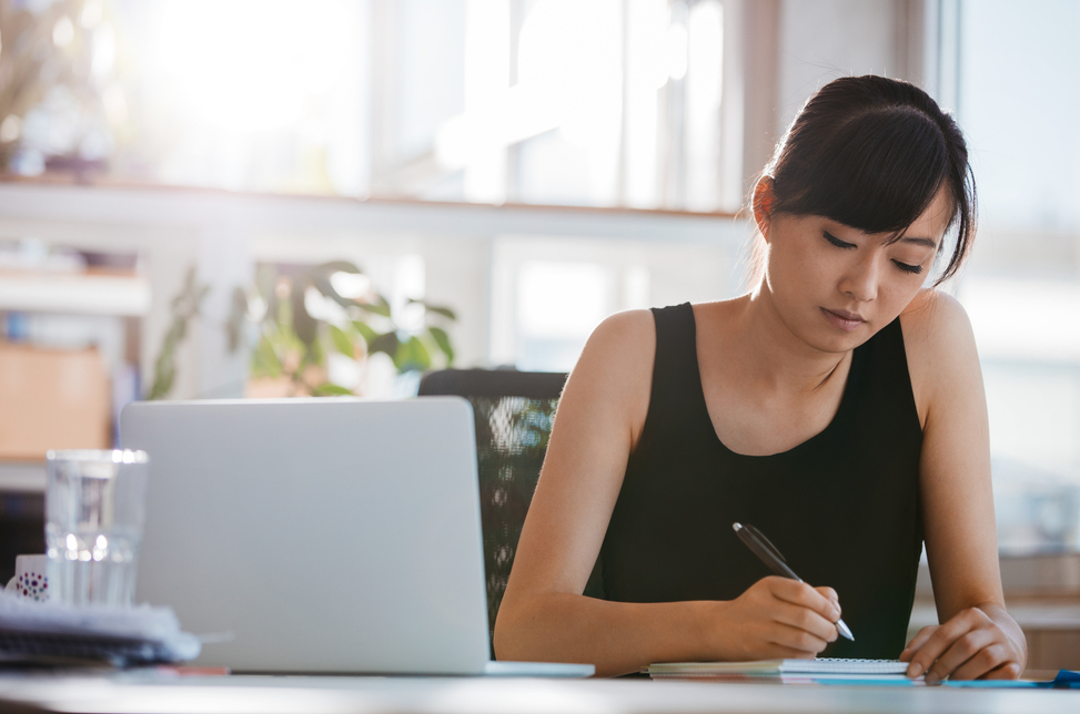 Shot of young woman sitting at a table and writing notes. Businesswoman working at her desk.