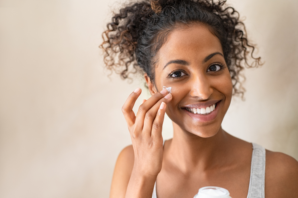Smiling african girl with applying facial moisturizer while holding jar and looking at camera. Portrait of young black woman applying cream on her face isolated on beige background with copy space.