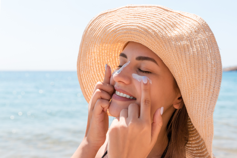Smiling woman in hat is applying sunscreen on her face.