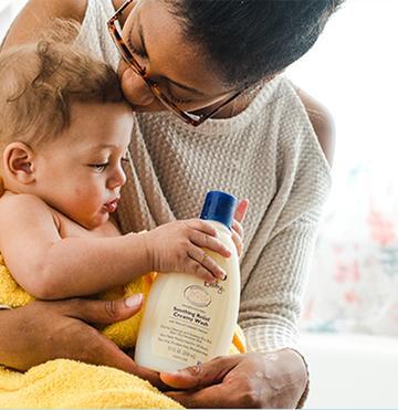 bebé y mamá con loción aveeno para bebés