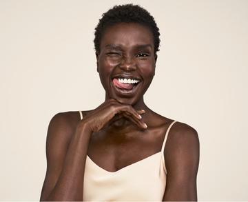 mujer guiñando el ojo y mostrando una piel luminosa con productos aveeno