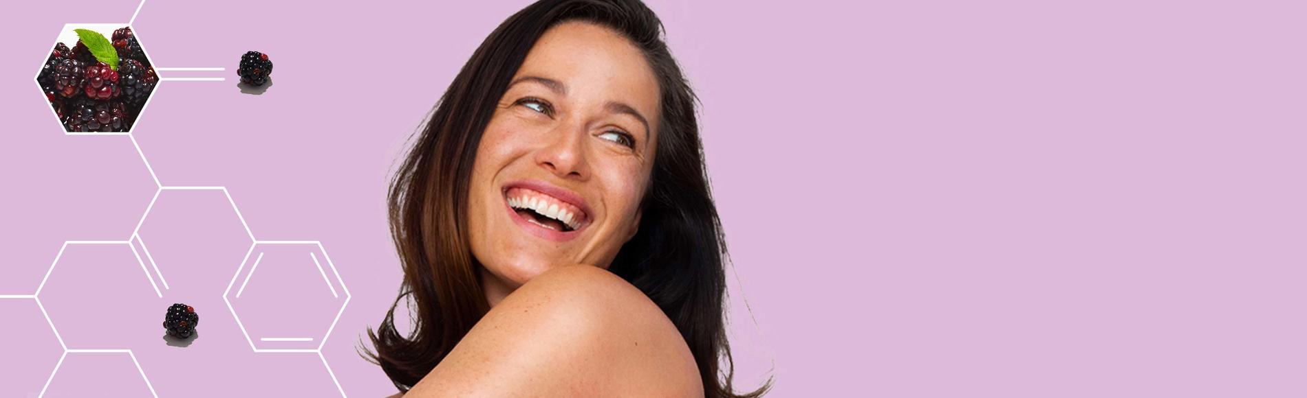 mujer sonriente usando los productos Absolutely Ageless de Aveeno