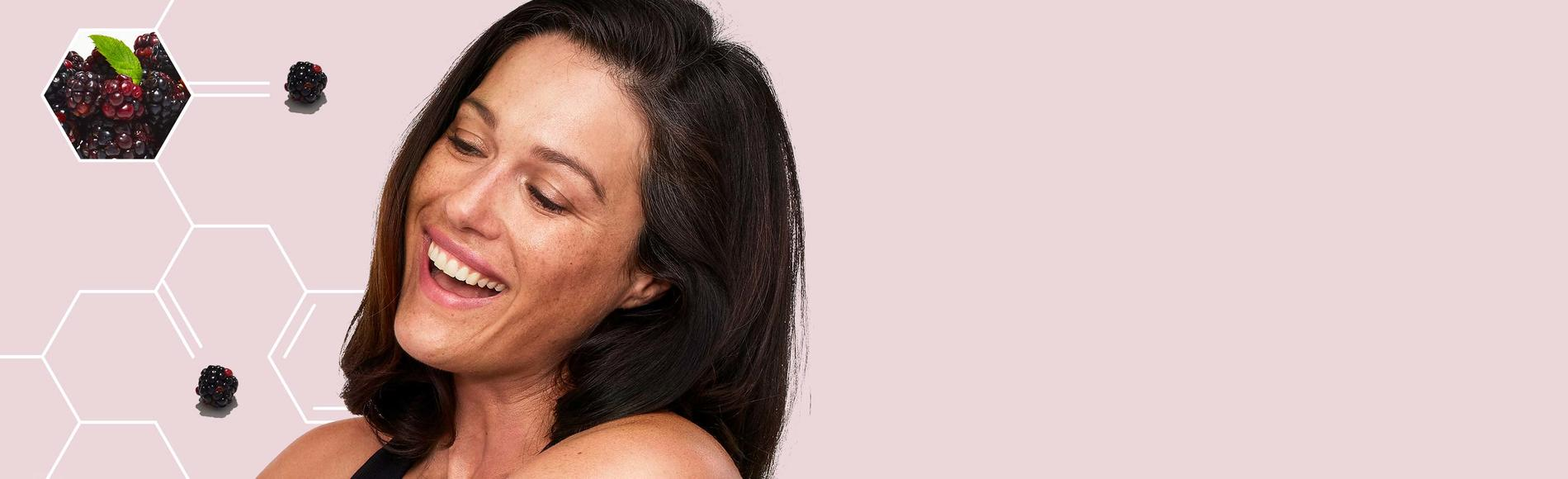 Mujer alegre que usa la loción corporal reafirmante Positively Ageless de Aveeno