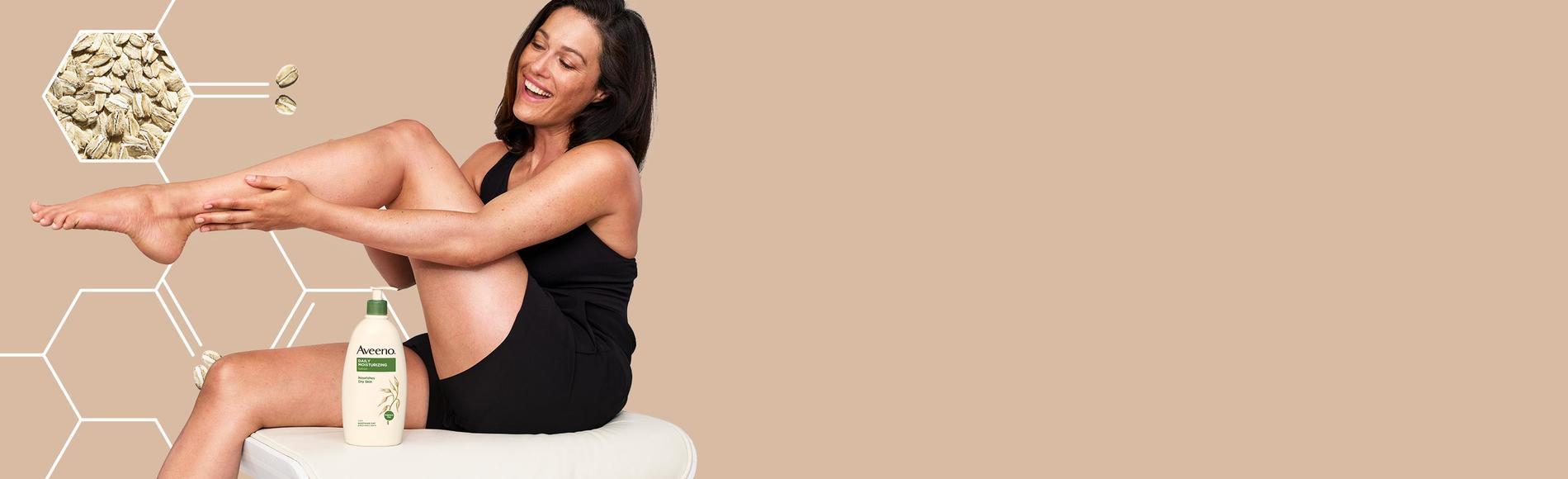 mujer contenta usando los productos Aveeno para el cuidado del cuerpo