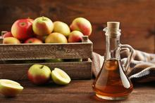 Jug of apple cider vinegar with red apple slices on a wooden table