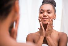 A woman looks at her skin in the mirror.