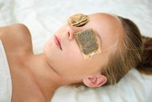 Woman using tea bags over her eyes