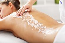 A woman receives a body exfoliation massage as salt is rubbed into her back.