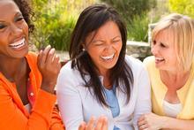 Three women laugh over a shared joke.
