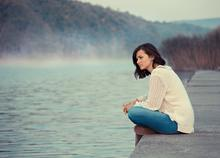 Woman sits on a dock thinking by the water