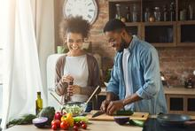 Two young adults laugh while cooking in the kitchen.