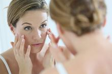 A young woman looks in the mirror and applies a skin cream.