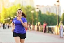 A woman smiles as she jogs.