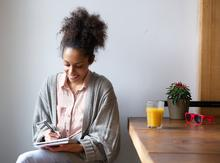 Woman writing down tasks on a self-care checklist