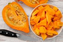 A quarter of a pumpkin, a knife and a bowl of pumpkin pieces sit on a white table