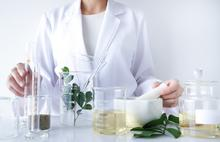A clinician in a white coat works at a table of beakers filled with natural skincare ingredients.