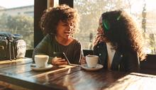Two women at a cafe table drinking from mugs laugh together.