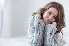Woman with dry skin wearing a sweater in winter.