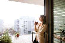 Woman looking out window onto an urban scene.