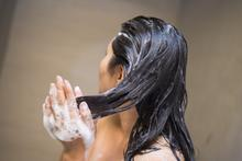 Woman washing hair in the shower.