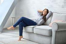 A smiling young woman embraces hygge sitting relaxed on a couch.
