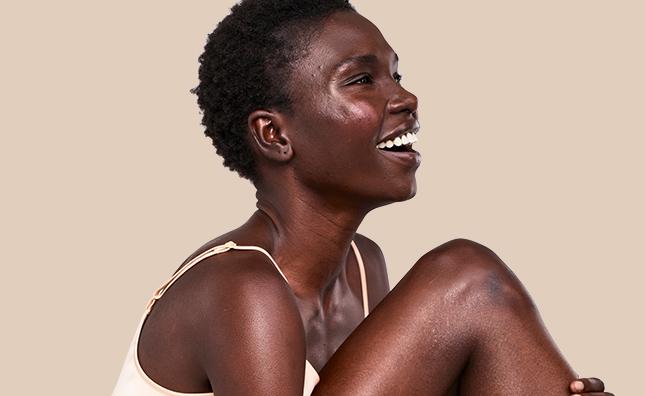 mujer sonriente con piel y rostro radiantes gracias a aveeno