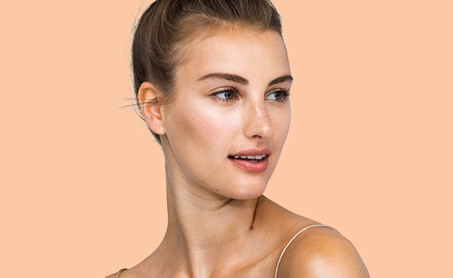 imagen de cerca de una mujer con piel radiante y maquillaje neutro