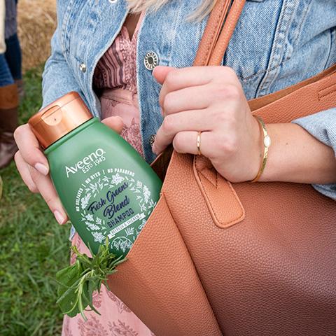 Mujer sosteniendo el champú Aveeno Fresh Greens