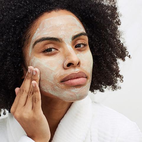 Mujer aplicándose la mascarilla Aveeno para el rostro